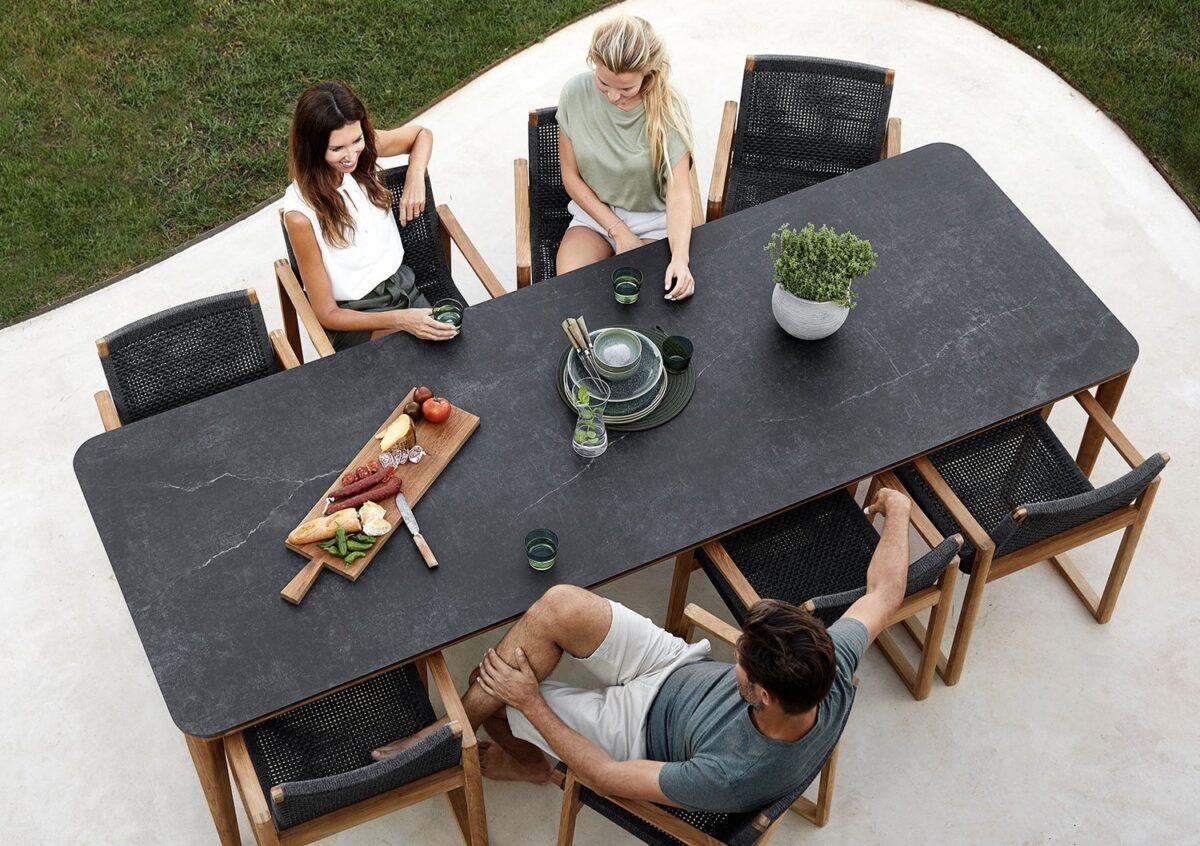 Ein Mann und zwei Frauen an einem dunkelgrauen Gartentisch