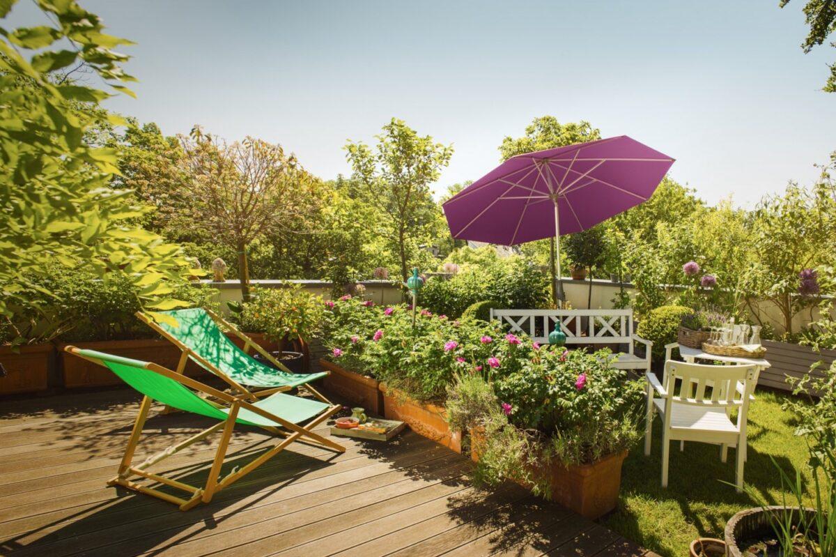 Sonnenschirm neben Gartenbank und Gartenstuhl
