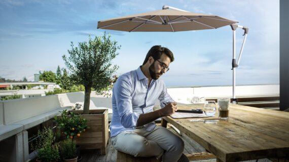 Mann sitzt an einem Holztisch auf einer Terrasse, Ampelschirm im Hintergrund